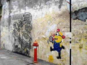 Malaysia | Straßenkunst an einer Hauswand aus Stein in George Town, Penang. Ein Feuerwehrmann als Comic in sein Megafon schreiend vor einem roten Hydranten