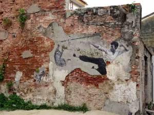 Malaysia | Straßenkunst an einer Hauswand in George Town, Penang. Für uns die Top-Sehenswürdigkeiten der Stadt. Ein Kung Fu Kämpfer im Sprung zur Verteidigung gegen zwei Katzen auf einer heruntergekommenengrau roten Steinmauer