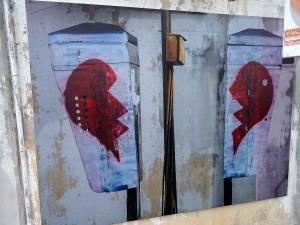 Malaysia | Straßenkunst in George Town, Penang. Einer unserer Top-Tipps der Stadt ist der Rundgang. Hier eine Hauswand an der 2 hellblau angemalte Kästen aufgehängt sind, die mit jeweils einer Hälfte eines roten Herzes bemalt sind