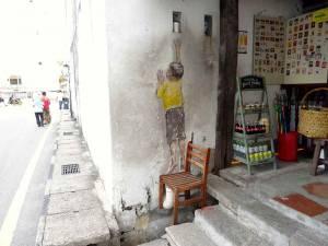 Malaysia | Straßenkunst in George Town, Penang. Ein an die Steinwand gezeichneter kleiner Junge im gelben T-Shirt streckt sich mit dem rechten Arm auf einem echten Holzstuhl stehend nach oben, um einen Becher greifen zu können. Rechts ein Shop der Getränke, etc. verkauft und links ein Pärchen das die Straße entlang geht