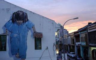Malaysia | An die Hauswand gemalte Straßenkunst in George Town, Penang bei Sonnenuntergang. Ein Mädchen im blauben Overall mit schwarzen Zöpfen stützt sich auf ihren Händen auf zwei Dächer von Fenstern