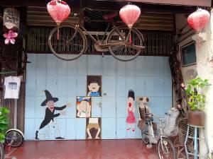 Malaysia | Straßenkunst in George Town, Penang. Ein hellblaues Tor, ein verrostetes Fahrrad und drei rote Lampen an der Decke aufgehängt, ein Zauberer mit einem schwarzen Zylinder auf dem Kopf und drei erschrocken wirkende Menschen. Rechts auf dem Boden eine verrostete Stahlbank sowie ein Fahrrad mit Kindersitz