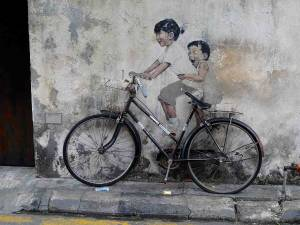 Malaysia | Straßenkunst in George Town, Penang. Ein an die Steinmauer gemaltes Mädchen auf dem Sattel und ein Junge auf dem Gepäckträger eines echten an die Steinmauer gelehnten, viel zu großen schwarzen Fahrrads