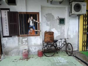 Malaysia | Straßenkunst in George Town, Penang. Ein Mädchen und ein Junge hinter einem offenen aber vergitterten Fensters die Arme ausstreckend. Ein schwarzes Fahrrad und ein Korb aus Holz stehen im Vordergrund