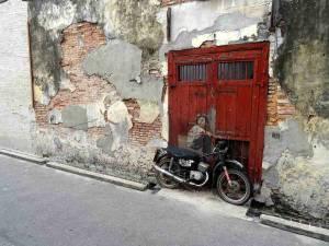 Malaysia | Straßenkunst in eine alte heruntergekommene Steinwand in George Town, Penang integriert. Ein Junge sitzt auf einem Moped angelehnt an ein rotes Tor und blickt gelangweilt auf die andere Straßenseite