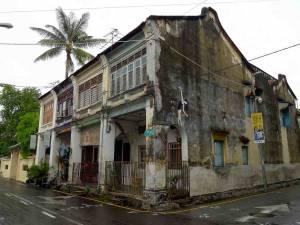 Malaysia | Straßenkunst in George Town, Penang, die sehr unauffällig in das Gesamtbild eines alten, heruntergekommenen Wohnhauses integriert ist.Ein dünnes Mädchen balanciert auf einem Torbogen