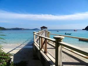 Malaysia | Vom weißen Strand führt ein Steg ins türkisfarbene Wasser zum Bootsanleger