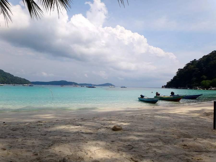 Malaysia | Perfekter Strand zum Schwimmen und Schnorcheln auf Perhentian Besar. Türkisfarbenes ruhiges Meer und ein paar Boote im Wasser. Weißer Sandstrand, blauer Himmel und im Inland sattgrüner Regenwald