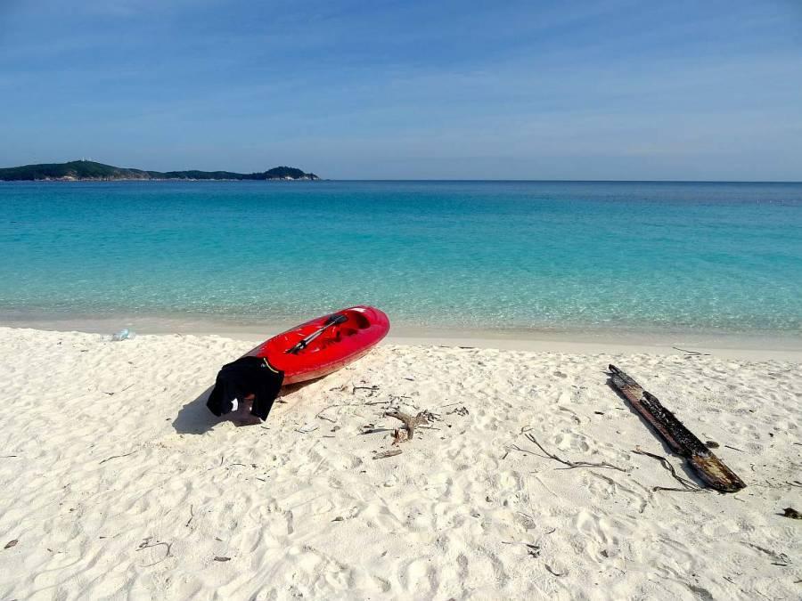 Malaysia | Rotes Kanu im weißen Sand mit dem türkisfarbenen Meer im Hintergrund am Strand liegend auf unserer Kanutour zum Turtle Beach auf Perhentian Besar