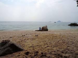 Malaysia | Karin sitzend auf einem Stein mit Blick auf das türkisfarbenes Meer am Strand namens Coral Bay auf Perhentian Kecil