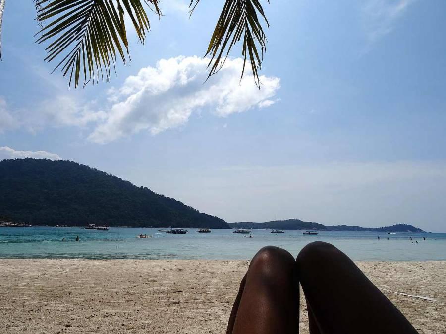 Malaysia | Perhentian Islands Entspannung am Strand unter Palmen bei strahlend blauem Himmel mit Blick auf das türkisfarbene Meer und einige Fischerboote