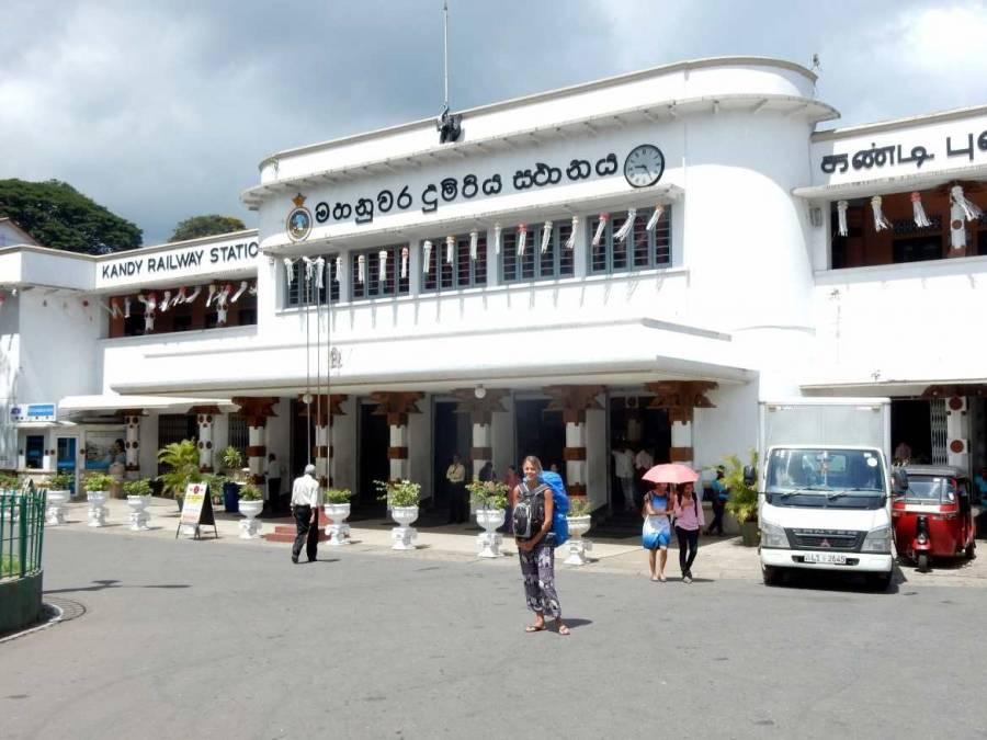 Sri Lanka   Karin steht vor dem weißen kolonialen Bahnhofs von Kandy