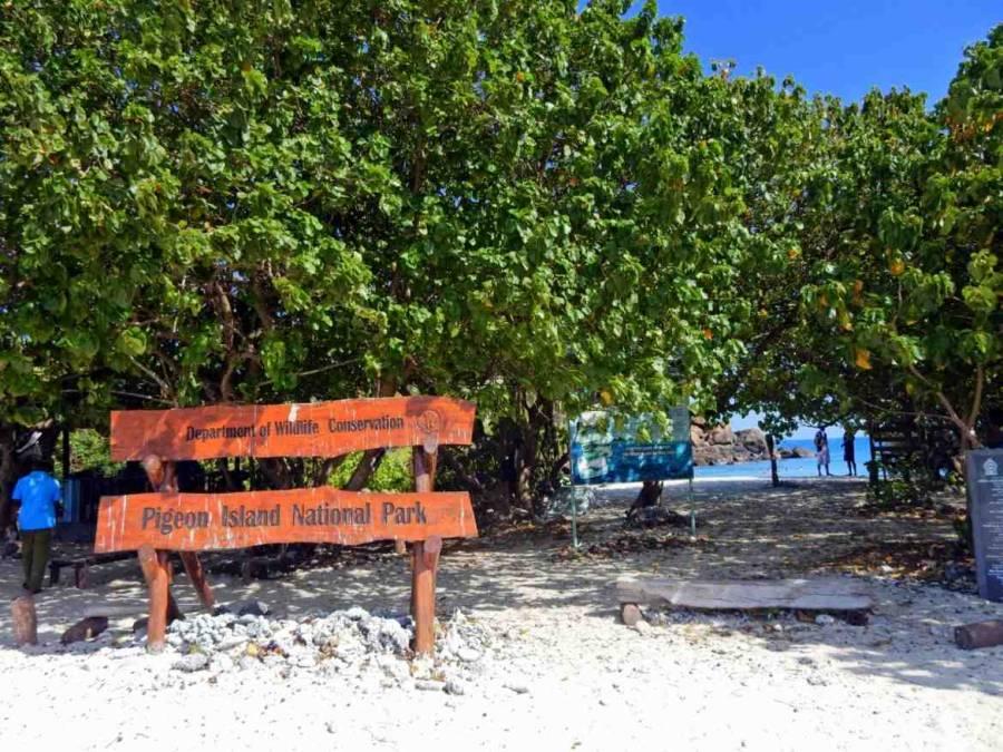 Sri Lanka | Ein großes Holzschild vor Bäumen am Strand heißt die Besucher willkommen auf Pigeon Island