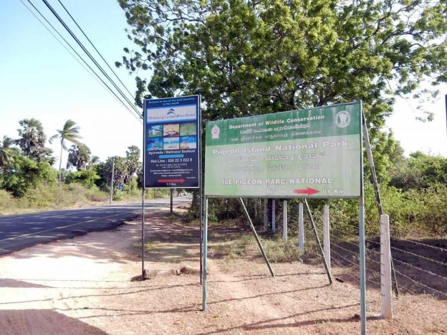 Sri Lanka | EIn großes grünes Schild markiert den 1. Wegweiser zum Bootableger nach Pigeon Island an der Hauptstraße