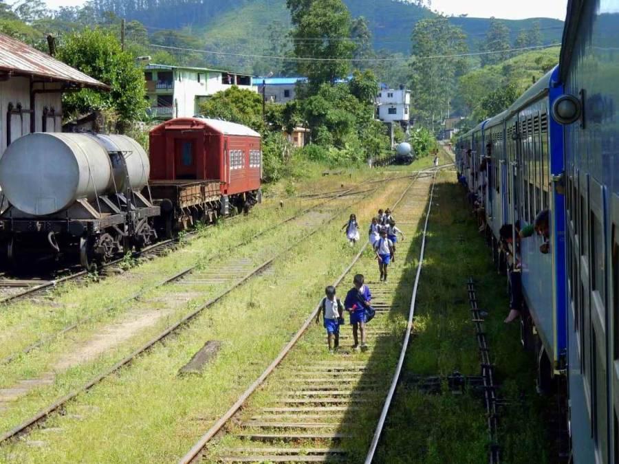 Sri Lanka | Der Zug von Kandy nach Ella hält im Bahnhof. Passagiere hängen begeistert aus den Fenstern und eine Gruppe von Schulkindern läuft entlang der Gleise
