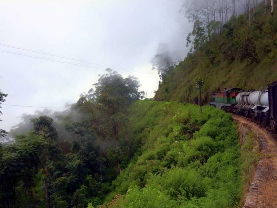 Sri Lanka | Zugfahrt von Kandy nach Ella im mystischen Nebel des Hochlandes. Eine alte Diesellok bahnt Ihren Weg entlang eines Abhangs über dem Urwald