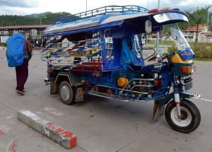 Ein typisch bunten Sammel-Tuk Tuk mit großer Ladefläche am Flughafen von Luang Prabang in Laos