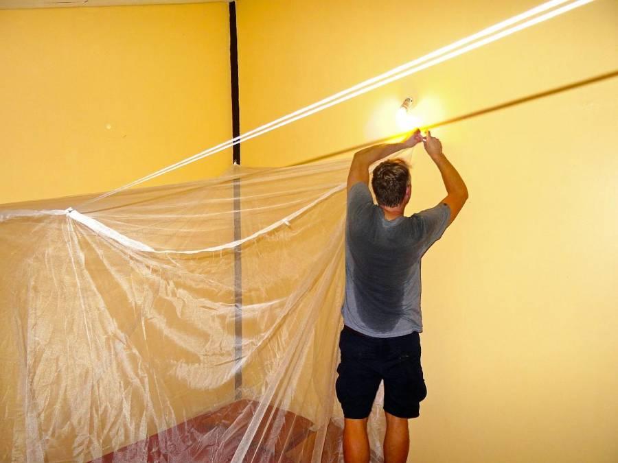 Mückenschutz | Henning der beim Aufhängen vom Moskitonetz in Schwitzen kommt