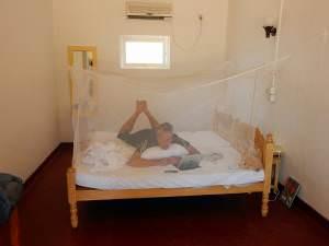 Mückenschutz | Ein kastenförmiges Moskitonetz, dass mit Schnüren und Haken angebracht wurde