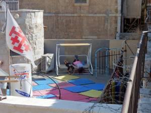 Jerusalem | interessante Orte: Ein Hinterhof in der Altstadt, zwei Jungen schaukeln auf einer Hollywood-Schaukel