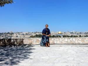Jerusalem | Karin sitzt auf einer Mauer, im Hintergrund die Altstadt