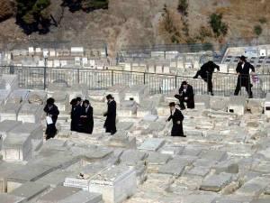 Jerusalem | Mehrere gläubige Juden klettern über einen Zaun und nehmen ein Abkürzung ins Kidrontal, dem bekannten jüdischen Friedhof