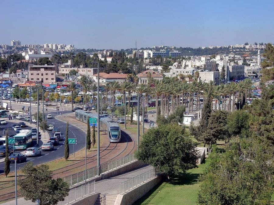 Jerusalem | Die moderne jerusalemer Trambahn vor den Toren Ost-Jerusalems und einem Palmenhain
