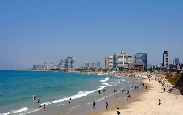 Tel Aviv | Belebter Stadtstrand von Tel Aviv mit einbrechenden Wellen vom Meer und einem Panoramablick auf die Hochhäuser des modernen Tel Aviv