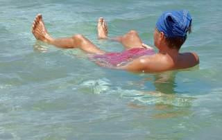 Totes Meer | Totes Meer | Baden im Toten Meer ist ein einmaliges Erlebnis. Henning liegt im Meer mit Kopfbedeckung gegen die Sonne