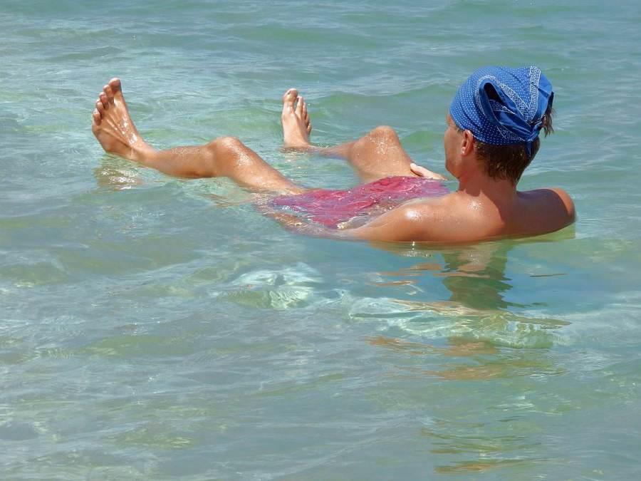 Totes Meer | Henning liegt im Meer mit Kopfbedeckung gegen die Sonne