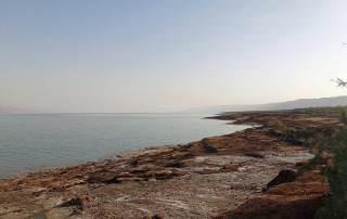 Totes Meer | Steinig brauner Strand mit Blick über das Wasser auf den Horizont