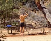 Tägliche Körperhygiene schützt vor zahlreichen Parasiten und Reisekrankheiten. Henning in der in der Wildnis mit einem Gartenschlauch duscht