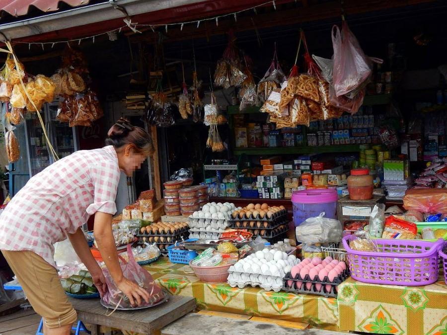 Laos | Frau richtet Ihre Verkäufe an ihrem Stand mit Lebensmitteln