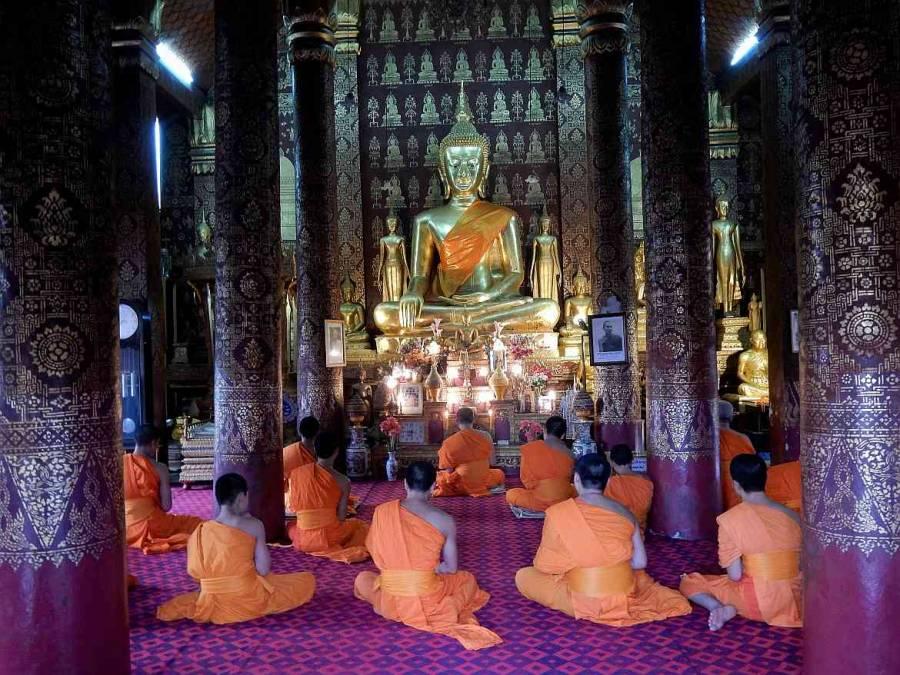 Laos | Am Boden vor einem großen Goldenen Buddha sitzende, betende Mönche im Wat Sene in Lunang Prabang