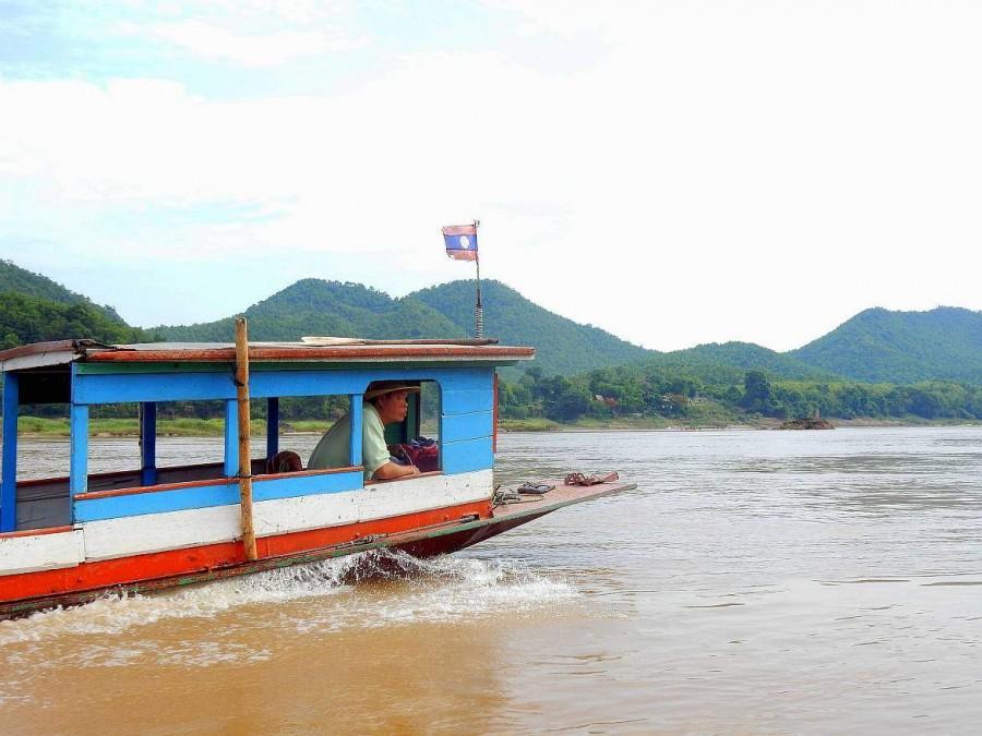 Laos | Der Kapitän bei der Arbeit im Boot auf Mekong. Kein seltener Anblick bei der Rundreise entlang des Mekong