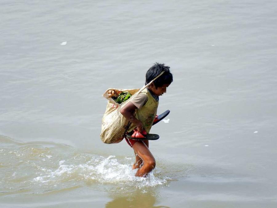 Ein Kind überquert denNam Khan Fluss mit seiner Ernte in einer Tasche auf dem Kopf