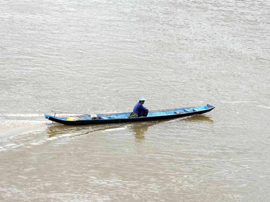 Menschen in Laos. Ein Mann auf seinem Boot auf dem Mekong