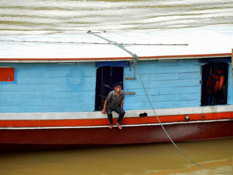 Laos | Mann genießt die Aussicht von seinem Boot auf dem Mekong