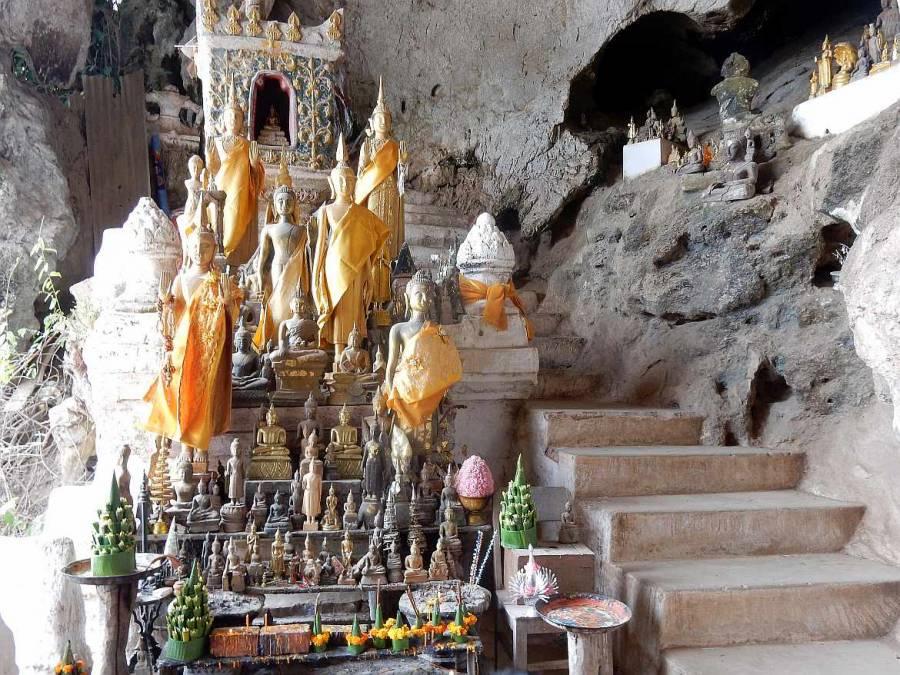 Eingang zur unteren Höhle Tham Thing gesäumt von verschieden großen Buddhas. Eine Treppe führt nach oben