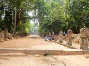 Kambodscha | Allee am Eingang zur Tempelanlage Banteay Kdei. EIn sandiger Weg führt in den Tempel, Wachmänner bewachen gelangweilt die Straße