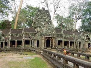 Kambodscha | Eingang zum Tempel Ta Prohm. Ein Junge mit Seiner Scchwester auf dem Rücken im Vordergrund