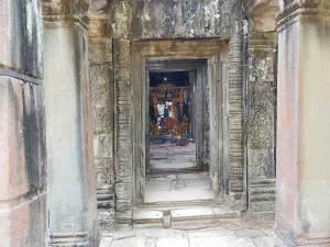 Kambodscha | Opferstelle im Tempel Ta Prohm. Zwischen den Mauern gelegene Buddha Statue mit Fahnen und Opfergaben