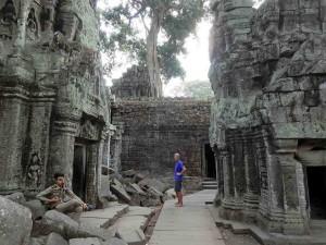 Angkor Wat Weltwunder | Weg durch die Ruinen des Ta Prohm Tempels. Henning im lila Shirt und ein Wachmann in Uniform gelangweilt auf einem Stuhl sitzend