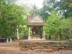 Kambodscha | Buddha im Angkor Archälogischen Park unter einem Dach sitzend aus Stein umgeben von grünen Urwaldpflanzen