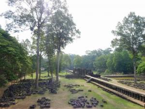 Kambodscha | Gelände beim Tempel Angkor Thom. Grüne Wiesen auf denen einzelene viereckige Temelsteine liege gesäumt von alten Steinmauern