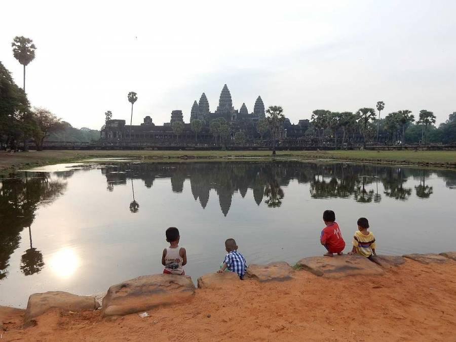 Kambodscha | Sonnenuntergang in Angkor Wat. Kinder sitzen mit Blick auf das Weltwunder am See indem sich der Tempel spiegelt