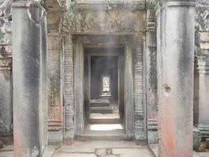 Kambodscha | Typischer Gang durch den Tempel Angkor Wat. Lange Gassen durch diverse Steinbögen mit Bildern und Fazierungen
