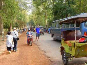 Kambodscha | Straße, die durch den Angkor Archälogischen Park führt. Henning in der Mitte gesäumt von Tuk Tuks, Mopeds und anderen Touristen