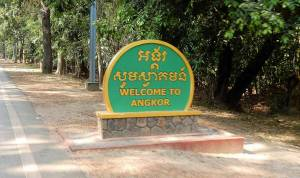 Kambodscha Angkor Wat | Willkommen im Angkor Archälogischen Park. Ein grün gelbes Schild am Straßenrand begrüßt die Touristen auf dem Weg zum Angkor Wat
