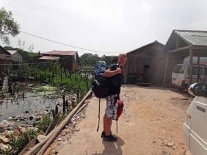 Kambodscha | Weg zum Bootableger nach Koh Thmei im Koh Kchhang Fishing Village. Henning mit Rucksack inmitten der staubigen Sandstraße